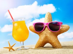 Starfish, sunglasses and cocktail on sand with sky in the background